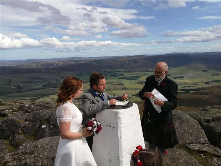 The happy couple sign the marriage certificate on the trig point.