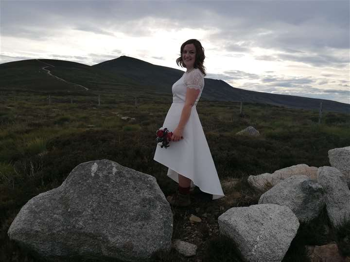 Sarah looks stunning in her wedding dress and hiking boots.