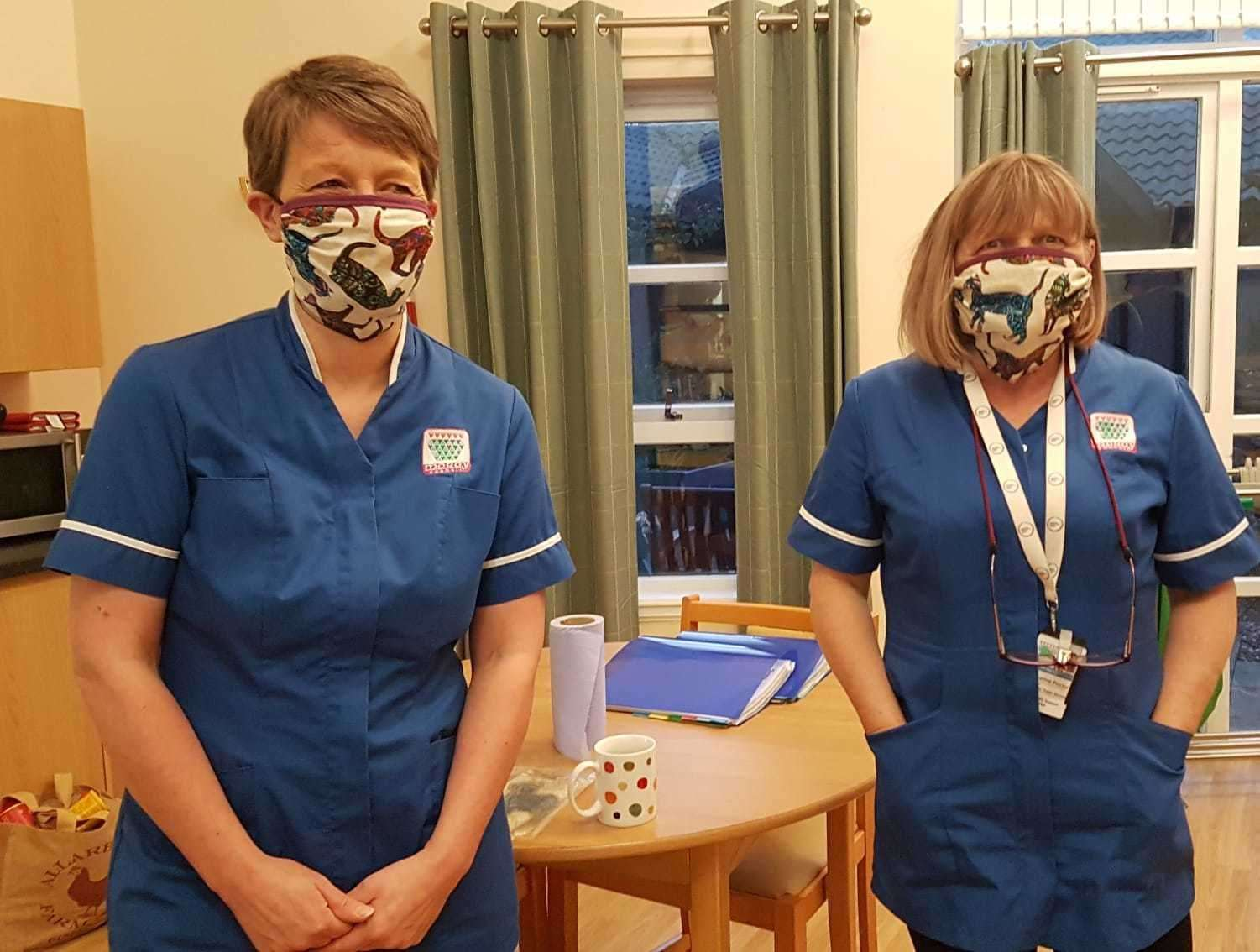 Two care workers model the masks made by the team.